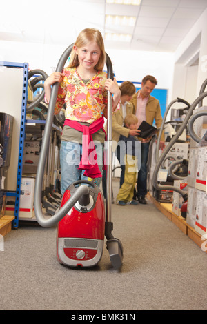 Little girl with vacuum cleaner - Stock Photo