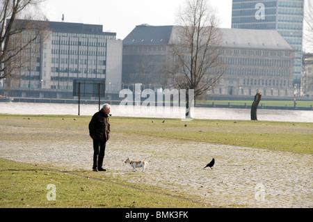 Man walking his pet dog, Dusseldorf, North Rhine-Westphalia, Germany. - Stock Photo