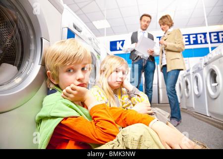 Children are bored of washing machines - Stock Photo