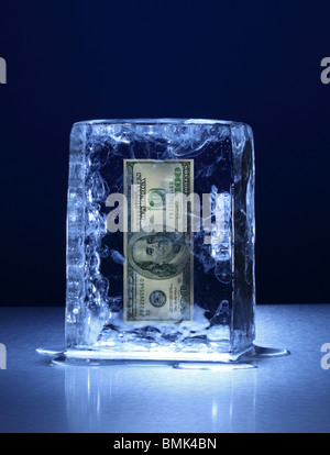 A frozen block of ice with a 100 US dollar banknote frozen inside on a metal surface - Stock Photo
