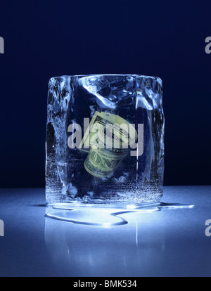 A frozen block of ice with a roll of US cuurency frozen inside on a metal surface - Stock Photo