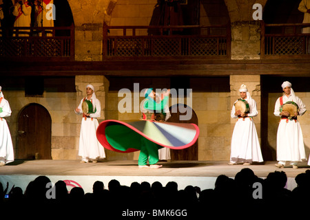 Whirling dervish performing a Sufi dance at the Al-Ghouri Mausoleum at night, Cairo, Al Qahirah, Egypt - Stock Photo