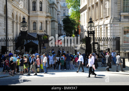Tourists on the Whitehall side of Downing Street in front of steel security gates controlled by Metropolitan police - Stock Photo