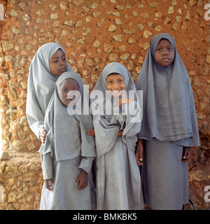 Young african muslim girls in Kenya in front of a mud hut in a traditional village. - Stock Photo
