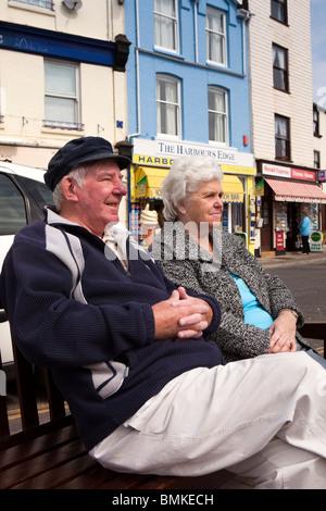 UK, England, Devon, Brixham Harbour, seafront, elderly couple relaxing in sunshine on quay - Stock Photo