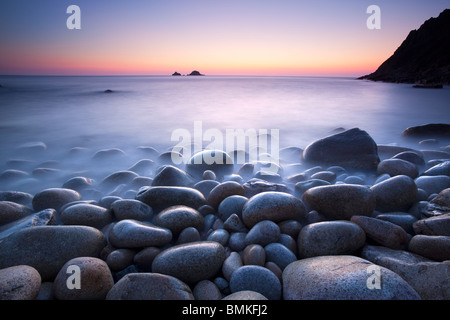 Boulders on beach at sunset Cornwall - Stock Photo