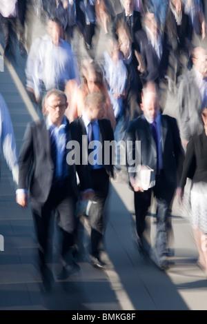 Commuters on London Bridge during rush hour - Stock Photo