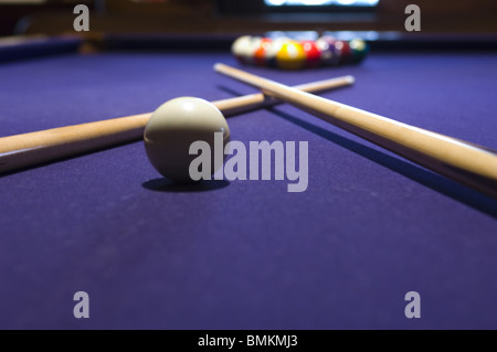 Close-up of a cue ball and pool sticks crossed over on a pool table - Stock Photo