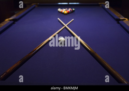 Close-up of pool sticks crossed over on a pool table - Stock Photo