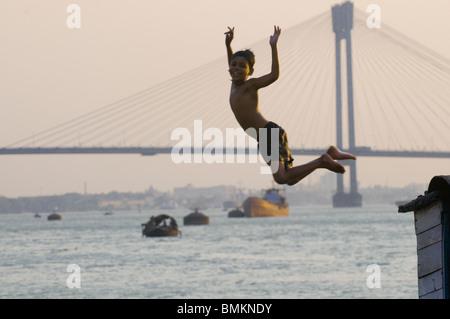 Boy jumping into sea, Howrah Bridge in background. Calcutta. India. - Stock Photo