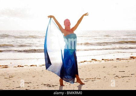 a blonde woman dancer dressed in blue silk is standing on teh beach on her toes with her arms raised above her head. - Stock Photo
