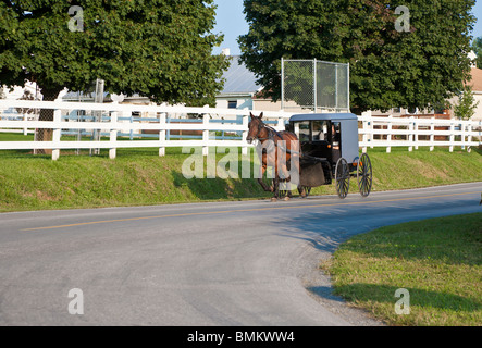 Lancaster County, PA - Sept 2009 - Amish family traveling past farmhouse in horse drawn buggy in Lancaster County - Stock Photo