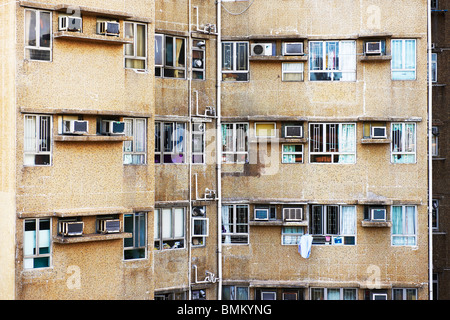 Back view of apartment buildings in Hong Kong, showing aged tile wall, drain pipes, dirty air conditioning and washing - Stock Photo