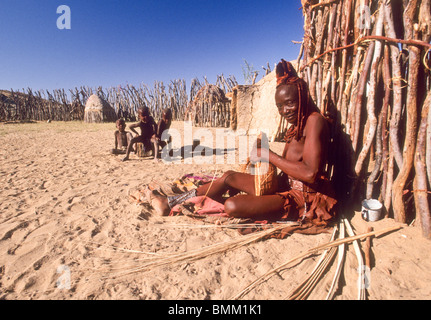 Namibia: Kaokoland, Hoarsib valley, near Puros Camp, Himba Valley, Himba Tribe woman weaving with children in background - Stock Photo