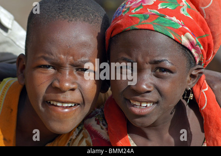 Niger. Zinder, Portrait of an african boy and an african girl with scarifications on her face, wearing a red scarf - Stock Photo