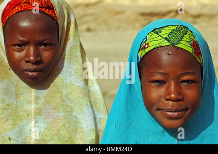 Niger. Zinder, Two african muslim girl friends wearing traditionnal and colorful dresses and wearing tchadors - Stock Photo