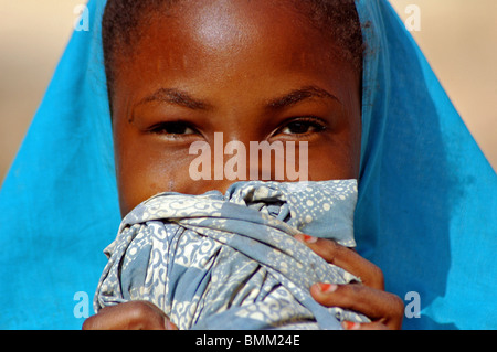 Niger. Zinder, Detail portrait of an african muslim girl wearing a turquoise tchador hiding behind a piece of cloth - Stock Photo