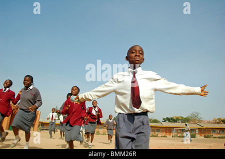 Nigeria, Jos, Schoolboys and schoolgirls in their purple and blue school uniform, running alltogether on a field. - Stock Photo