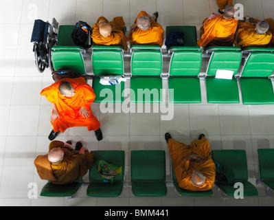 A group of orange cladded Thai Monks sitting on green benches awaiting their flight to Zurich Kloten Airport (ZRH/LSZH) - Stock Photo