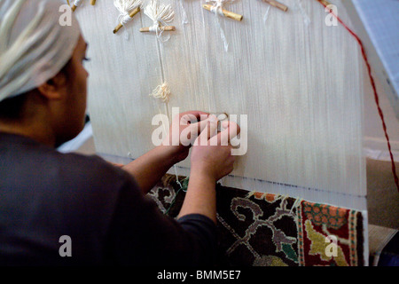 A young woman making a carpet in Turkey - Stock Photo