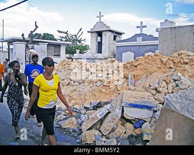 A woman walks past Port au Prince cemetery after the Haiti earthquake - Stock Photo