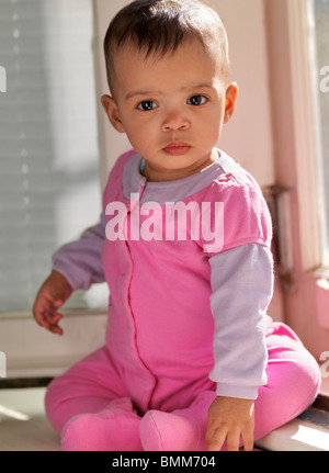Cute seven month old baby girl sitting on a window sill - Stock Photo