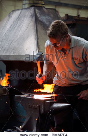Vocational skills learning to be a blacksmith at Holme Lacy college. Blacksmith hammering a hot piece of metal on - Stock Photo