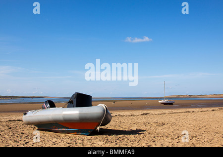 A small boat sits on the sand on instow beach on a sunny day with a yacht in the background and a person walking - Stock Photo
