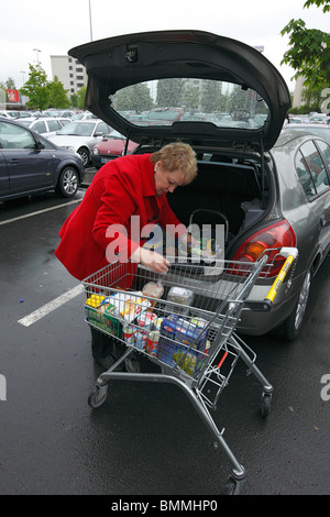 woman with a cart during shopping in a supermarket, goods will be loaded into a boot of a passenger car, D-Oberhausen, - Stock Photo