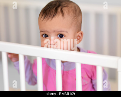 Cute seven month old baby girl in a crib - Stock Photo