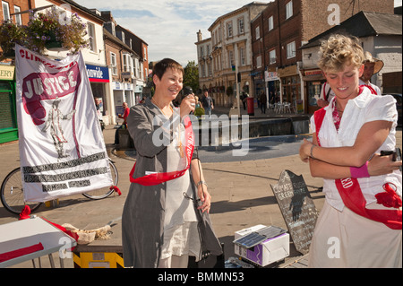 Climate Rush On Tour: Aylesbury.  Tamsin Omond listens as Caroline Lucas speaks in front of the Justice banner - Stock Photo