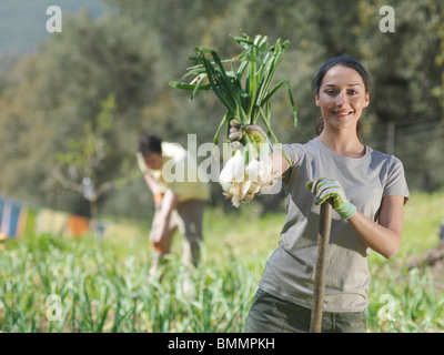 Woman showing freshly picked onions - Stock Photo