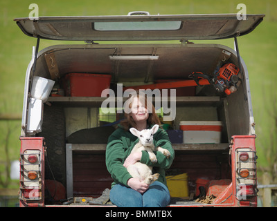 Woman sitting in van boot holding lamb - Stock Photo