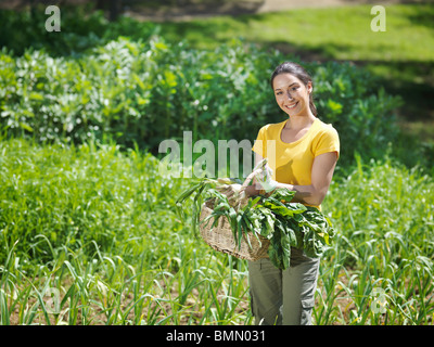 Woman with freshly picked veg in basket - Stock Photo