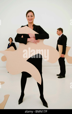 Happy Women holds large jigsaw piece - Stock Photo