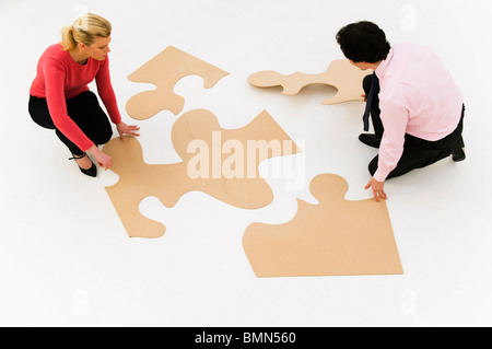 Business people work at finishing puzzle - Stock Photo