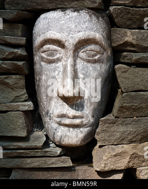 A sculpted face peers out of a cairn at the North Carolina Botanical Garden in Chapel Hill. - Stock Photo