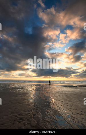 A lone waker silhouetted beneath a dramatic winter sky over Dunraven Bay in Southern Wales - Stock Photo