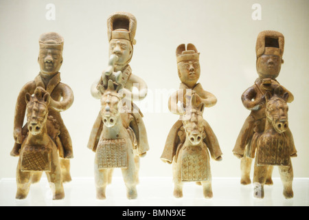 Four bronze statues of men riding horses wearing ancient Chinese military armor and tall hats. - Stock Photo