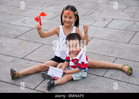 Children waving flags at the celebration of the Olympic Games 2008 in the streets of Beijing, China. Asia - Stock Photo