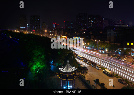 Light trails from car headlights captured on a busy main road in Changsha city, Hunan province, China, against city - Stock Photo