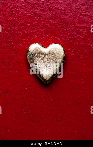 Gold heart shape against red texture metal painted background - Stock Photo