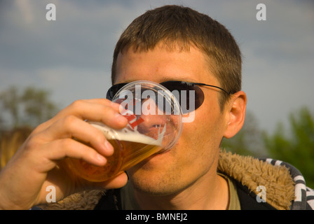 Russian man in his 30s drinking beer out of plastic cup Zizkov district Prague Czech Republic Europe - Stock Photo