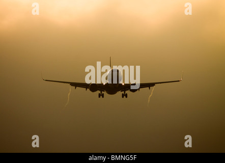 Silhouette of a Boeing 737-800 aircraft at sunset - Stock Photo