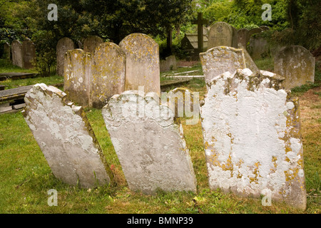 Uneven headstones show signs of their age in a churchyard in England. - Stock Photo