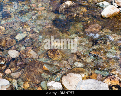 Pebbles in the water flowing in a stream close up overhead view - Stock Photo