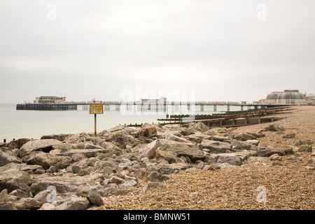 A seagull sits on a sign on the beach and looks towards the pier at Worthing in West Sussex, England. - Stock Photo