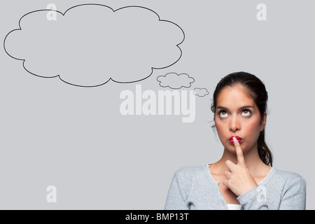 Woman with big brown eyes looking upwards thinking with blank thought bubbles above her head, isolated on white - Stock Photo
