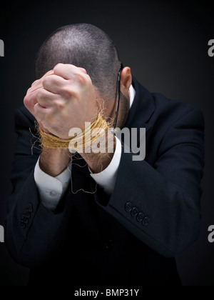 A man on a suit is raising his tied hands. - Stock Photo