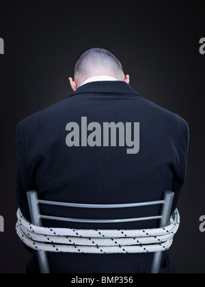 A businessman is tied up on a chair turning his back to the camera. - Stock Photo